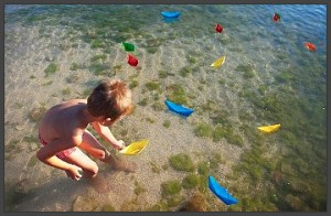 kid-playing-with-paper-boats